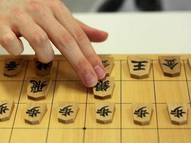 Mano cogiendo pieza del tablero de shogi